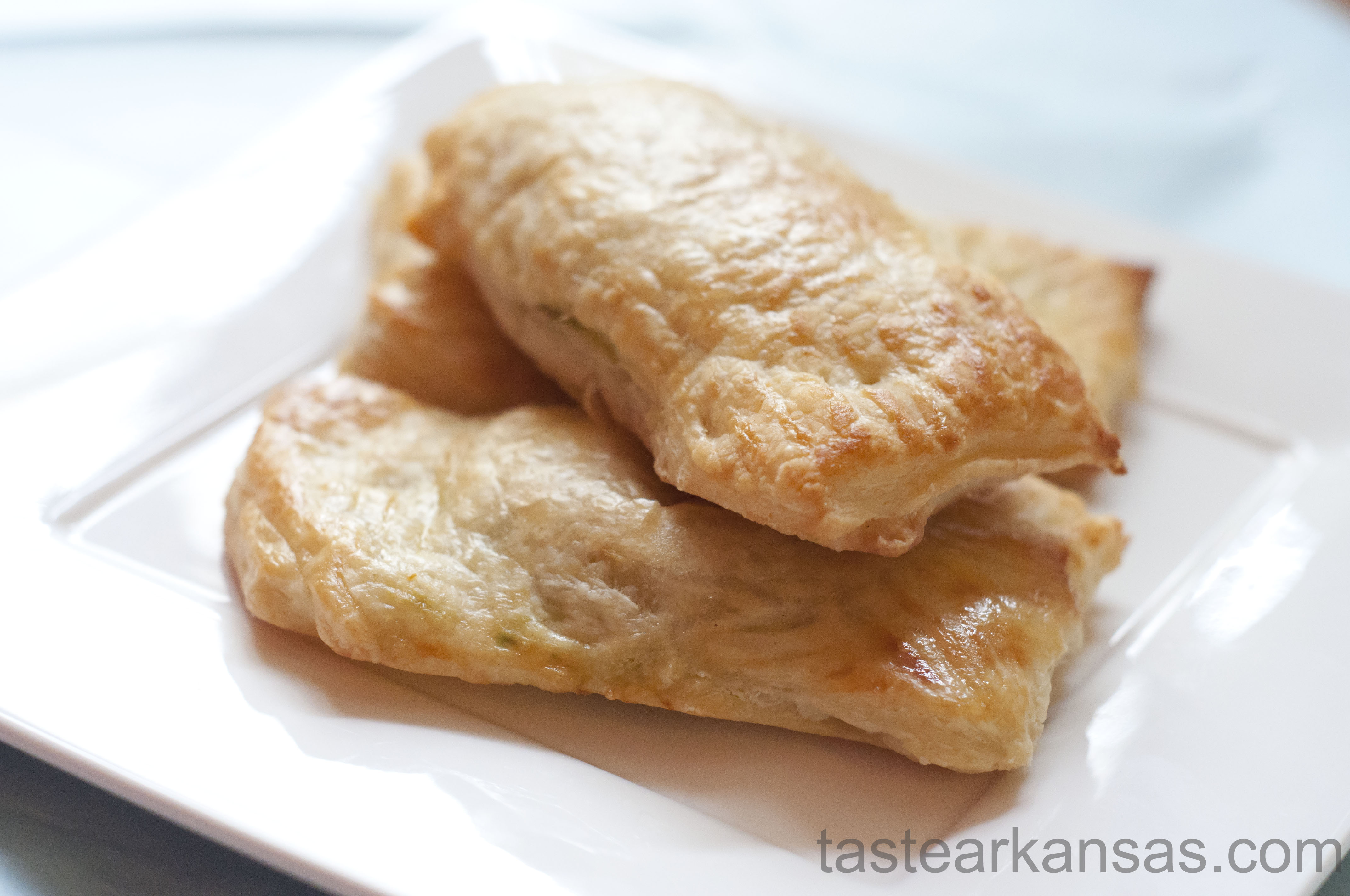 This picture shows a lightly browned, puff pastry packet that is filled with a warm mixture of avocado, cream cheese and salsa. The edges are brown and the pastry is buttery, flaky and delicious.