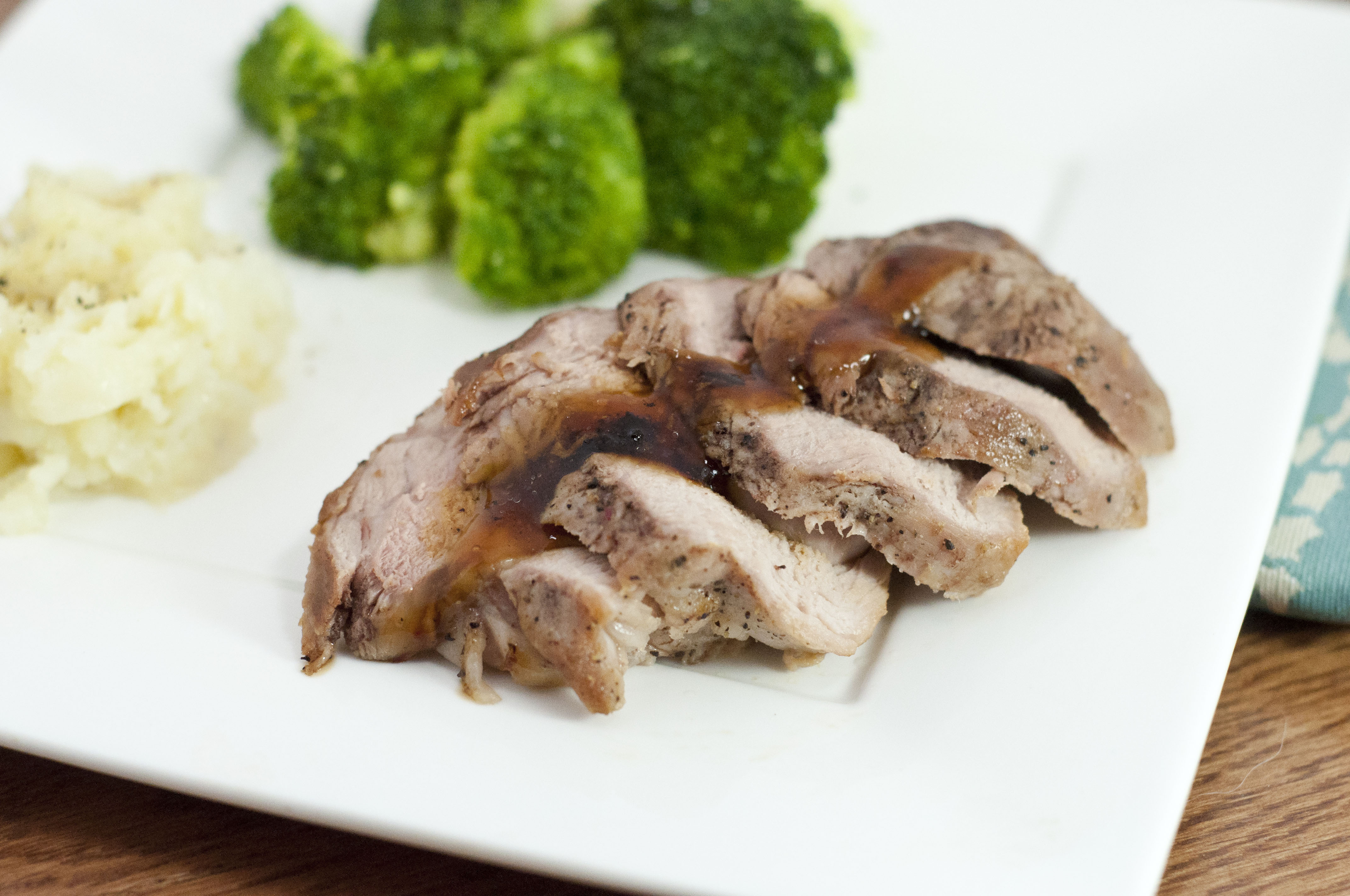 an image of brined teriyaki pork tenderloin with broccoli and potato in the background