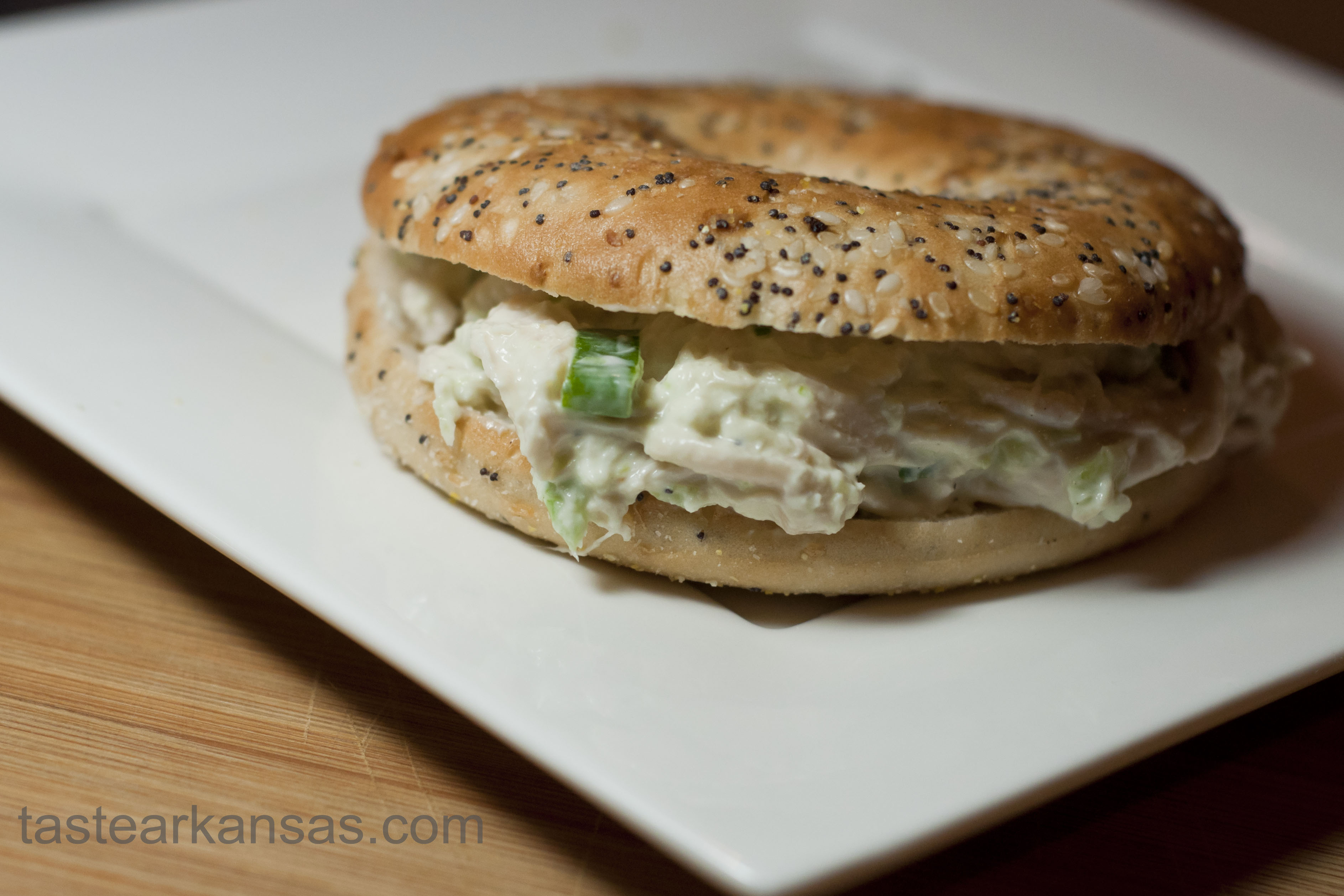 this image is of a creamy chicken salad sandwich on a bagel thin